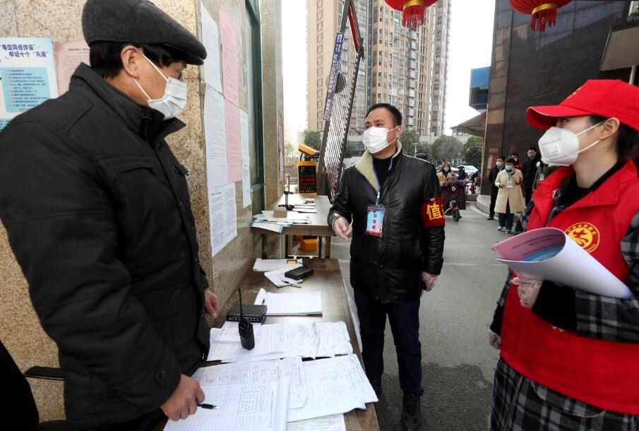 图3   2月12日,沈陈紫迪和父亲陈明一起在一个居民小区前了解人员进出体温测量和登记情况。 (2)