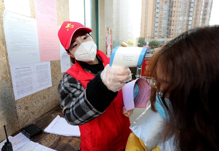 图19  2月12日,沈陈紫迪在小区门前为来往居民测量体温。