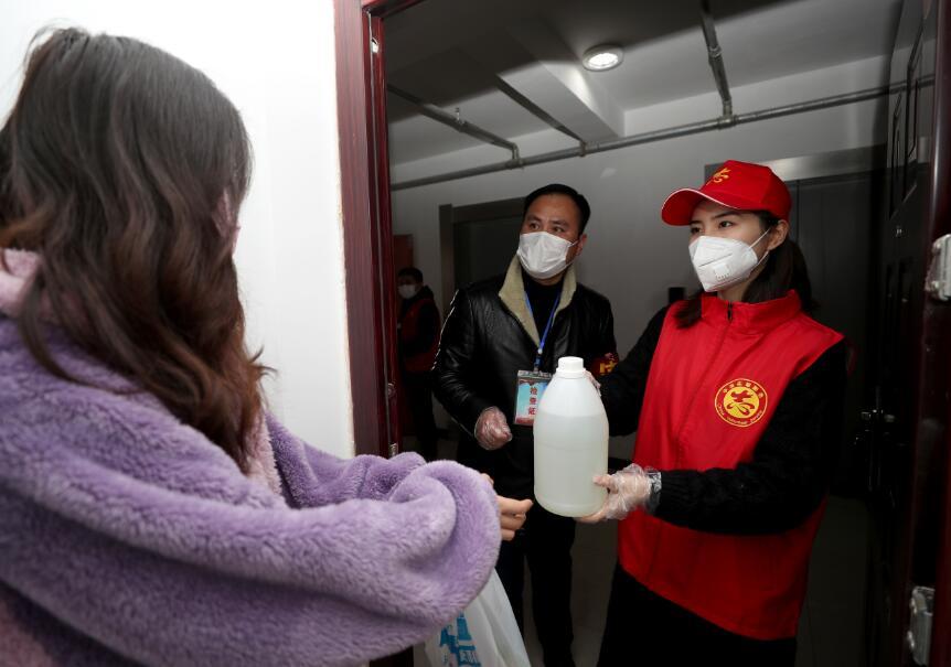 图11  2月12日,沈陈紫迪和陈明为一户居家观察的居民送去消毒液和生活用品。